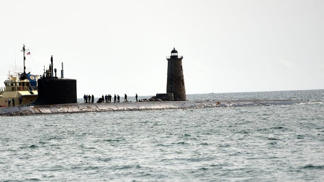 The Virginia class fast-attack submarine USS Texas (SSN 775) passes Whaleback Lighthouse in Kittery, Maine, as seen from the shore of the New Castle Common as it heads to Portsmouth Naval Shipyard on Wednesday.
