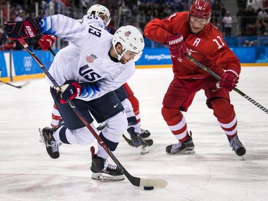 U.S. men's hockey team, forward Ryan Gunderson, retrieves