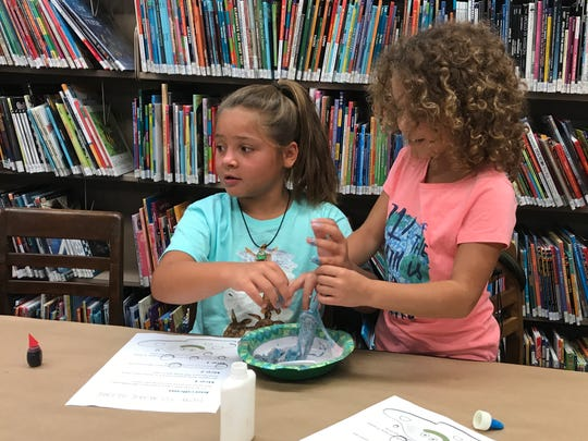 Nina Caputo, 10, at left, and Olivia Willis, 7, mush together their slime at the Cedar Grove Library on July 14, 2017.