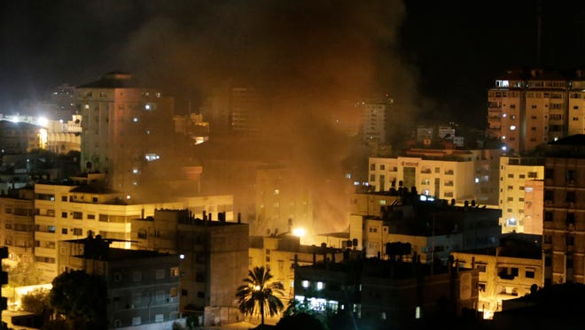 Smoke rises from a vehicle destroyed by an Israeli strike in Gaza City on Saturday, July 26.