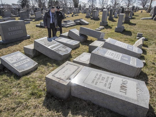 Northeast Philadelphia Police Detective Timothy McIntyre and a Philadelphia police officer look over tombstones that were vandalized at Mount Carmel Cemetery on Sunday, Feb. 26, 2017, in Philadelphia. More than 100 headstones have been vandalized at the Jewish cemetery in Philadelphia, damage discovered less than a week after similar vandalism in Missouri, authorities said. (Michael Bryant/The Philadelphia Inquirer via AP)