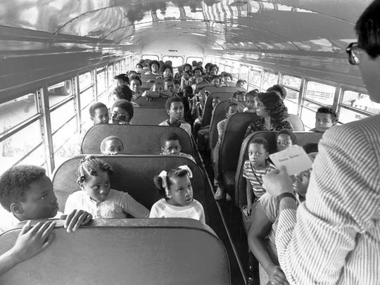 Former IPS pupils arriving at Valley Mills Elementary School wait for name tags before getting off the bus as school begins in Decatur Township in 1998. Court-ordered cross-district busing began in Decatur and Perry Townships and Lawrence Township.