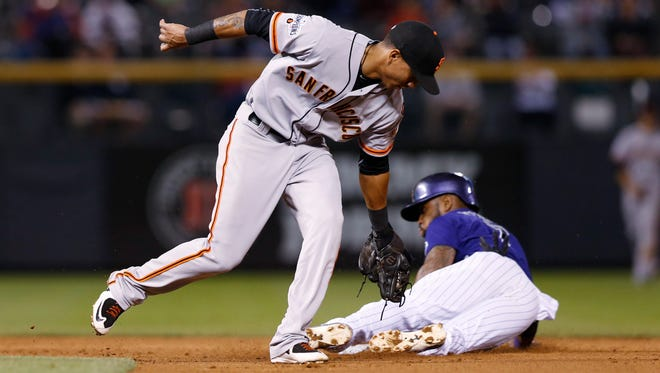 San Francisco Giants shortstop Ehire Adrianza, left, fields the throw as Colorado Rockies' Jose Reyes steals second base in the fourth inning of a baseball game, Thursday, Sept.. 3, 2015, in Denver. (AP Photo/David Zalubowski)