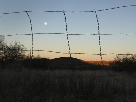 A barbed wire fence stretches along the U.S.-Mexico