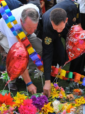 Orlando Mayor Buddy Dyer and Orlando Police Chief John Mina lay down roses at a memorial during a vigil honoring the victims of a mass shooting at Orlando's nightclub Pulse, as they gather at the Dr. P. Phillips Center for the Arts in Orlando, Fla., Monday, June 13, 2016. (Craig Rubadoux/Florida Today via AP) MANDATORY CREDIT