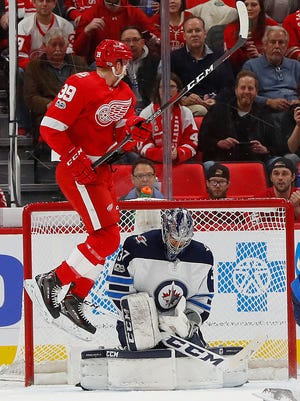 Winnipeg Jets goalie Connor Hellebuyck (37) stops a shot as Detroit Red Wings right wing Anthony Mantha (39) jumps in front of the net in the first period of an NHL hockey game Tuesday, Dec. 5, 2017, in Detroit.