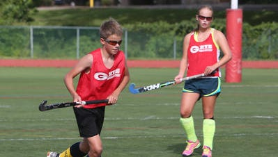 Phile Govaert with sister Fusine in background during 2015 Rye varsity field hockey practice.