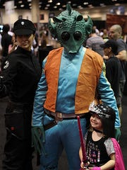 Briana (left) and Adam Petersen pose with a young fan at a celebration event for the 501st Legion in Orlando.