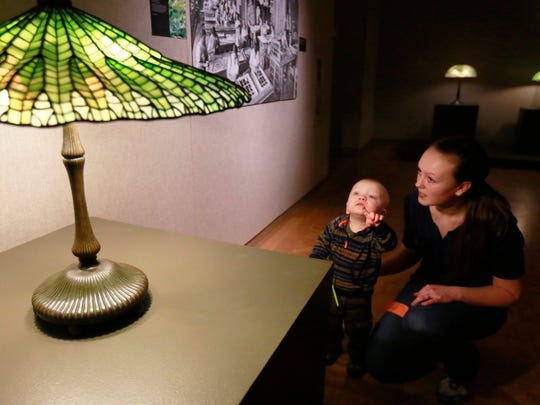 Joel Gilray, 17-month-old, points at a Tiffany stained glass lamp while his mother Kim looks on Friday in an exhibit of Tiffany Glass at Leigh Yawkey Woodson Art Museum in Wausau.
