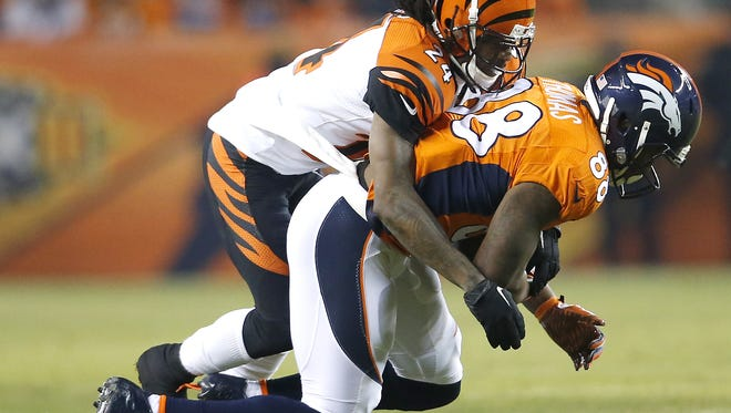 Cincinnati Bengals cornerback Adam Jones (24) tackles Denver Broncos wide receiver Demaryius Thomas (88) in the first quarter during the Week 16 NFL game between the Cincinnati Bengals and the Denver Broncos, Monday, Dec. 28, 2015, at Sports Authority Field at Mile High in Denver, Colorado.