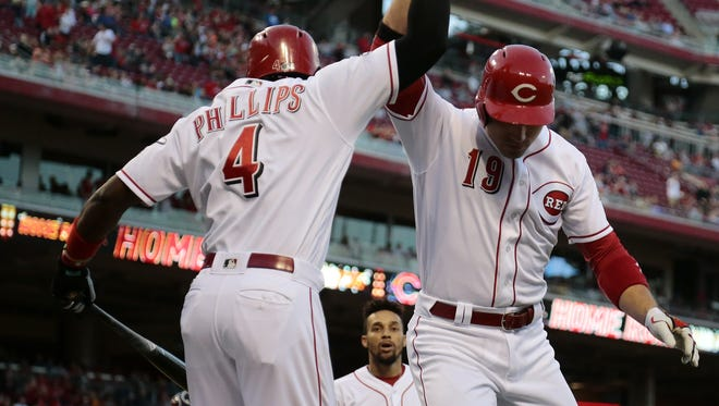 Cincinnati Reds second baseman Brandon Phillips (4) and first baseman Joey Votto (19) celebrate Votto's two-run home run in the bottom of the fourth inning of the MLB game between the Cincinnati Reds and the Cleveland Indians at Great American Ball Park in downtown Cincinnati on Thursday, May 19, 2016. After four innings, the game was tied 2-2.