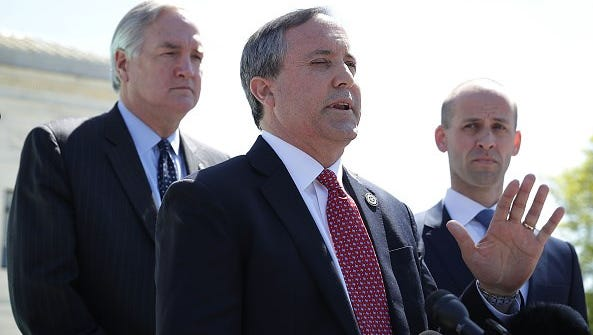 Texas Attorney General Kenneth Paxton speaks to members of the media as Texas Solicitor General Scott Keller, right, listens in front of the U.S. Supreme Court on April 18, 2016 in Washington, DC. On May 25, Paxton announced that Texas and 10 other states are suing the federal government over President Obama's directive to force public schools to allow transgender students to use bathrooms that correspond to their gender, rather than birth, identities.