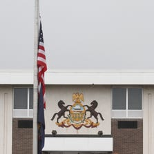 The U.S. flag is flown at half-staff outside of the Pennsylvania State Police headquarters in Dunmore, Pa., on Sept 13, 2014. A late-night ambush outside a state police barracks in Pennsylvania's rural northeastern corner left one trooper dead and another critically wounded, and authorities scoured the densely wooded countryside and beyond on Saturday looking for the shooter or shooters. (AP Photo/ The Times-Tribune,  Jake Danna Stevens) ORG XMIT: PASCR108