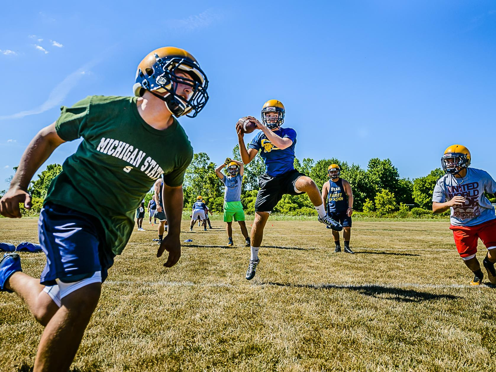 Grand Ledge quarterback Nolan Byrd ,center, recovers a high snap as he and his teammates run a play during the first practice of their fall camp Monday August 8, 2016 in Grand Ledge. KEVIN W. FOWLER PHOTO