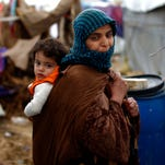 In this Monday, Jan. 4, 2016, file photo, a Syrian refugee carries a baby on her back at a refugee camp in the town of Hosh Hareem, in the Bekaa valley, east Lebanon.