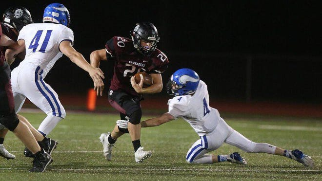 Buhler's Sam Elliott (20) runs past Winfield's Parker Smith (41) and Braden Ledford (4) during their game Friday night. Buhler defeated Winfield 21-9.