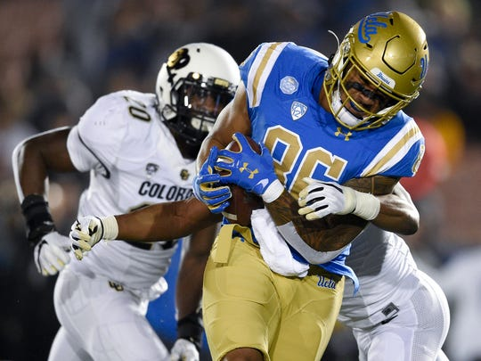 UCLA tight end Devin Asiasi , front, catches a pass for a touchdown while defended by Colorado safety Mikial Onu during the first half of an NCAA college football game in Los Angeles, Saturday, Nov. 2, 2019. (AP Photo/Kelvin Kuo)