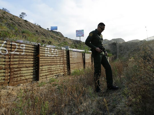 In this June 22, 2016 photo, a Border Patrol agent stands near a border structure in San Diego. Lawmakers, union leaders and polygraph experts contend that the use of lie detectors in the application process has gone awry and that many candidates are being subjected to unusually long and hostile interrogations, which some say can make people look deceptive even when they are telling the truth. (AP Photo/Gregory Bull)