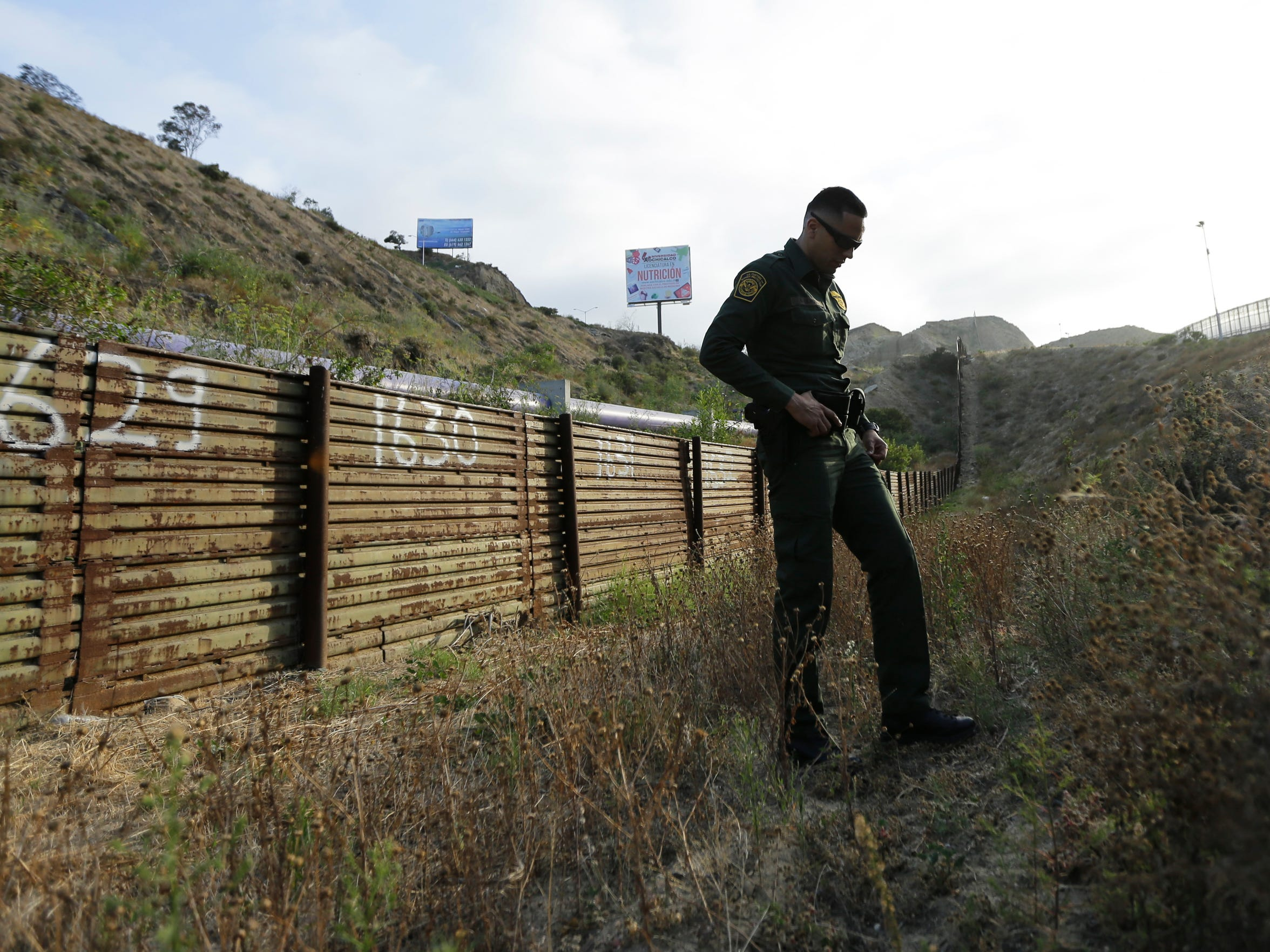 In this June 22, 2016 photo, Border Patrol agents stands near a border structure in San Diego.