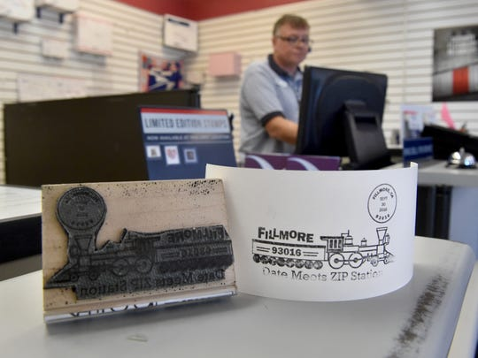 Richard Davidson of the U.S. Postal Service helps customers at the post office in Fillmore on Thursday, the day before this commemorative postmark becomes available. Post office boxes at the location share a ZIP code with Friday's date, 93016, which is being recognized with the special postmark that will be available upon request for a month.