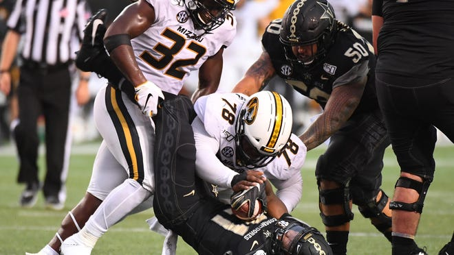 Vanderbilt running back Keyon Brooks (21) is tackled by Missouri linebacker Nick Bolton (32) and defensive lineman Kobie Whiteside (78) during a game Oct. 19, 2019, at Vanderbilt Stadium in Nashville, Tenn.