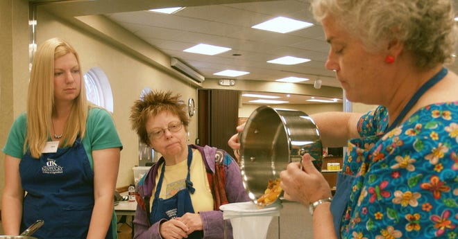 Diane Mason, right, shows how to extract the juice from peaches at the Jam and Jelly Making Class at the Boone County Cooperative Extension Service in Burlington.