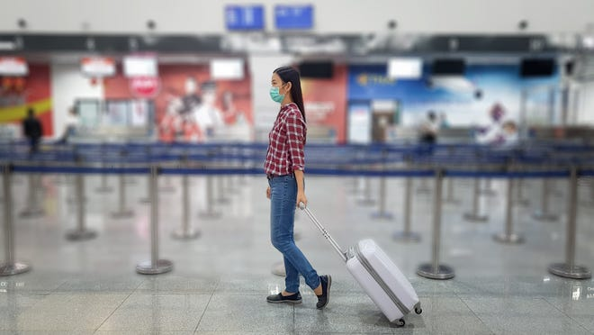 A traveler with a mask on walks through an airport.
