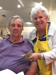 Shirley Posner, a member of the Bingo Committee, awards prize money to Keith Strong a visitor to Marco Island from Woodstock, Illinois, the big winner at Monday Night Bingo at the Jewish Congregation of Marco Island.