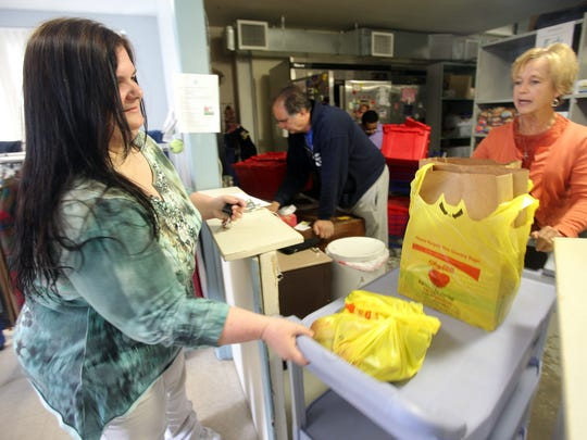Christine Metscher, right, a volunteer with People to People, gives Valerie Van Houten of Nyack her monthy supply of food from the food pantry at People to People in Nanuet on April 8.