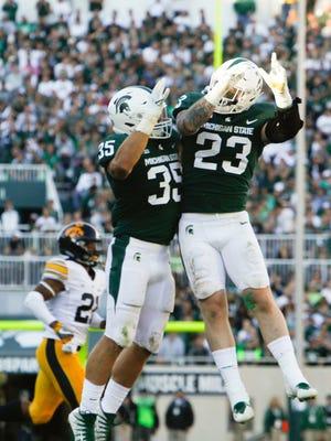 MSU's Joe Bachie and Chris Frey, 23, celebrate an MSU touchdown against Iowa Saturday, Sept. 30, 2017, at Spartan Stadium in East Lansing.