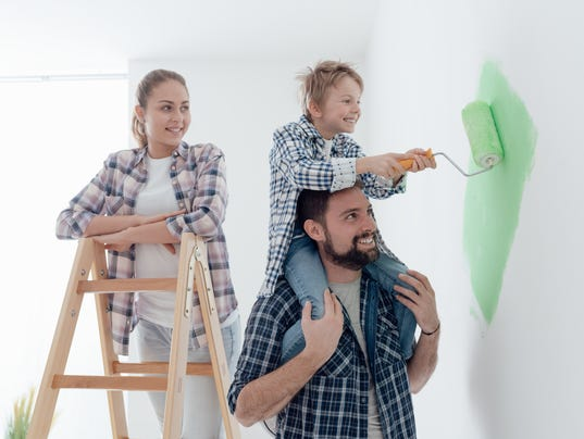 Family painting walls together