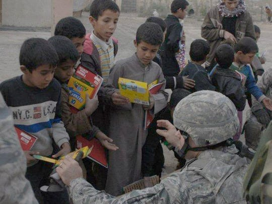 Master Sgt. Brent Baker hands markers and crayons to Iraqi children Dec. 16, 2010, at Ur Elementary School near Tallil Air Base, Iraq. Sergeant Baker is an Echelon Above Division-Advise and Train munitions adviser.