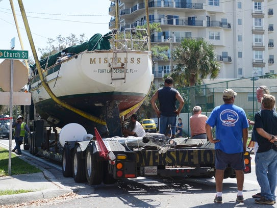 Work crews lift a boat named Mistress onto a trailer