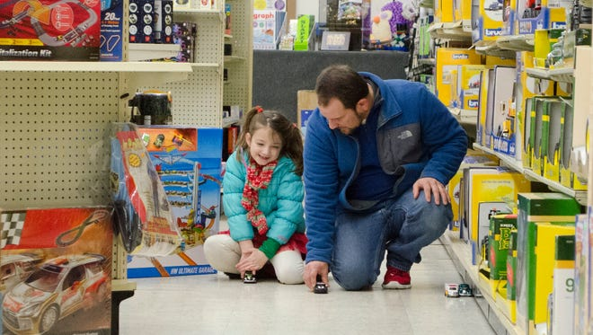 A man teaches a child under his care how to race toy cars at Veach's Toy Station in Richmond, Ind. on Tuesday, Dec. 20, 2016.