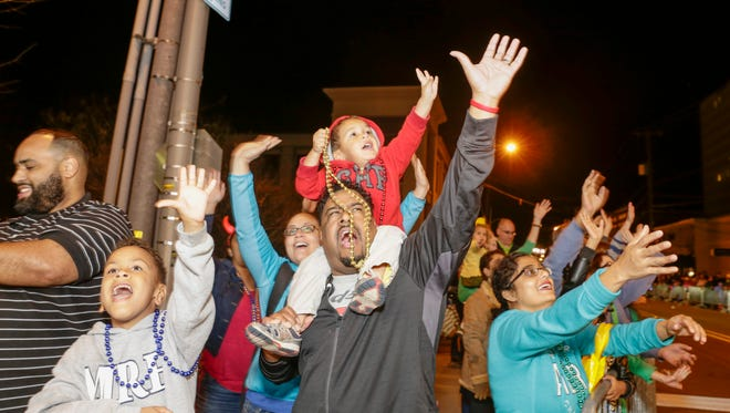 Jacob Rougeaux calls out for beads with his son, Noah, during the Bonaparte Mardi Gras parade Saturday, Feb. 25, 2017 in downtown Lafayette.