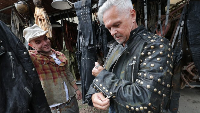 Mario Frulio (left), with King Cruiser from Italy, talks with customer Franz Joseph Promock of Austria. The Italian clothing company will make you a custom leather motorcycle jacket that looks like it's been ripped and shredded on asphalt, complete with patches and oil stains.