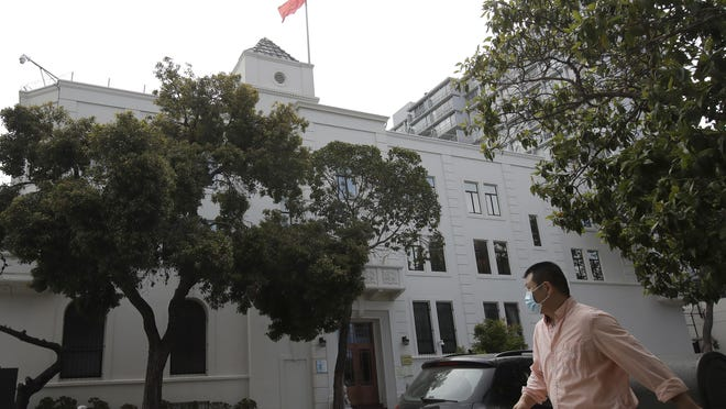 A man walks across the street from the Chinese Consulate in San Francisco, Thursday, July 23, 2020. The Chinese consulate in San Francisco is harboring a Chinese researcher who the FBI says lied about her military background.
