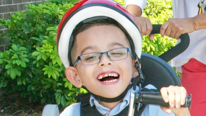 The smile on Anthony Castillo's face says it all as he tries out his adaptive bicycle for the first time at Avalon Elementary School.