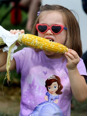 Isabella Nichols, Noblesville, enjoys a roasted ear of corn at the Hamilton County 4-H Fair in 2014.