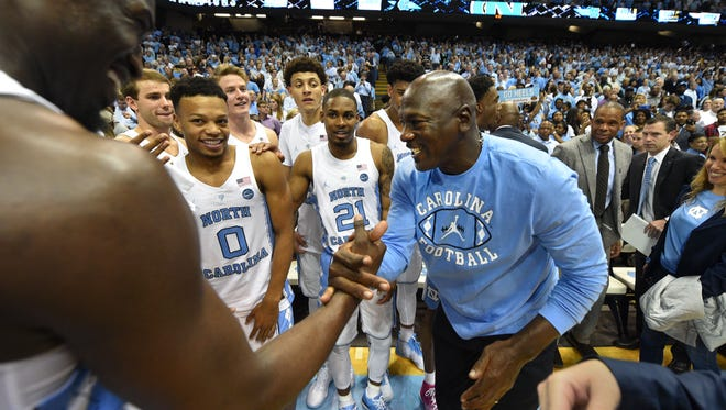 Mar 4, 2017; Chapel Hill, NC, USA; Former North Carolina Tar Heels player Michael Jordan congratulates forward Theo Pinson (1) after the game. The Tar Heels defeated the Blue Devils 90-83 at Dean E. Smith Center. Mandatory Credit: Bob Donnan-USA TODAY Sports ORG XMIT: USATSI-337356 ORIG FILE ID:  20170304_bsd_sd2_771.JPG