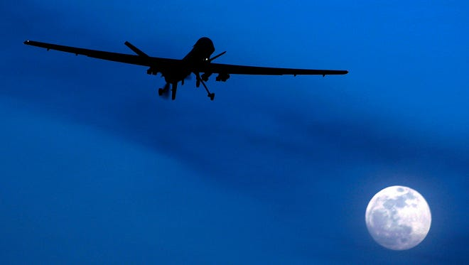 An unmanned U.S. Predator drone flies over Kandahar airfield in southern Afghanistan on a moonlit night Jan. 24, 2013.