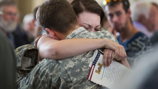 Sgt. Brittney Poore hugs her wife Bianka Desure (right) as they say goodbye after an Aug. 11, 2013, deployment ceremony for members of the 150th Engineer Company in New Castle, Del.