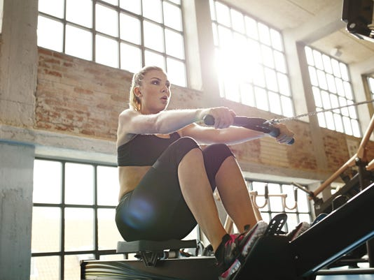 Young woman doing exercises on fitness machine