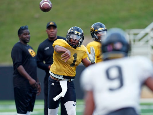 Grambling's senior quarterback Devante Kincade (1) passes to wide receiver Devohn Lindsey (9) during practice, Thursday, Nov. 16, 2017, at Eddie G. Robinson Memorial Stadium in Grambling, La. Kincade, who played two seasons at Ole Miss, says playing football at a Historically Black College or University is an experience to savor. Playing at an HBCU is not just about entertaining halftime shows the schools are known for, it's about community. (AP Photo/Rogelio V. Solis)
