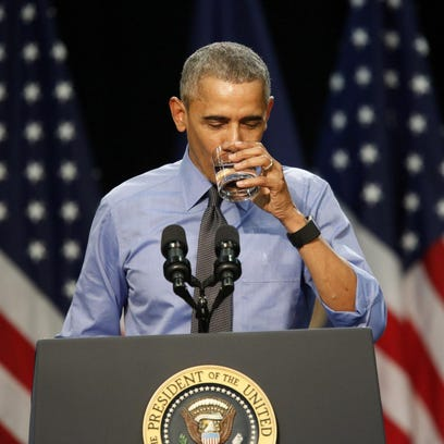 President Barack Obama drinks a glass of water as he