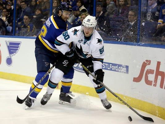 San Jose Sharks' Chris Tierney, right, looks to pass as he is hit by St. Louis Blues' Kevin Shattenkirk during the first period of an NHL hockey game Thursday, Feb. 4, 2016, in St. Louis. (AP Photo/Jeff Roberson)