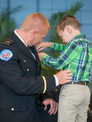 Matthew Coverdale is pinned by his sons Cooper and