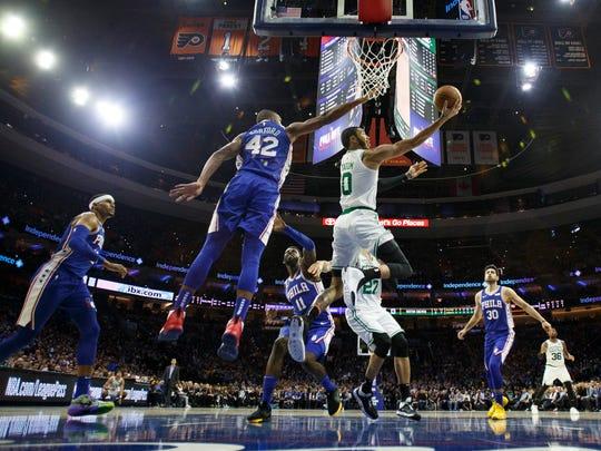 Boston Celtics' Jayson Tatum, center right, goes up for a shot against Philadelphia 76ers' Al Horford, center left, during the first half of an NBA basketball game Wednesday, Oct. 23, 2019, in Philadelphia. (AP Photo/Chris Szagola)