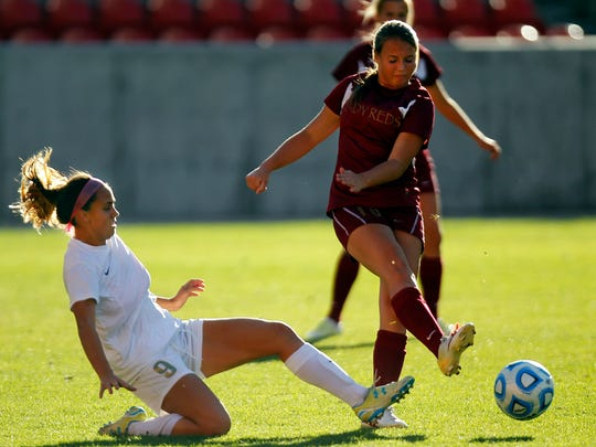 Cedar's Bailey Robinson kicks the ball away from Logan's Demi Lopez in the Girls 3A State Soccer Championship at Rio Tinto Stadium in Sandy on Saturday.