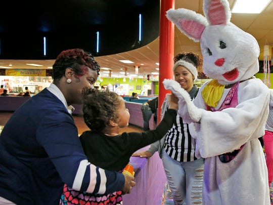 "Aalyah McCowns, center, gives the Easter Bunny, Tashawn Carter, right, high five during Skateland's ""Biggest Skate Party of the Year,"" Sunday, April 16, 2017.  With extended hours and two hours free admission, skaters new to the activity and seasoned, enjoyed the fun."